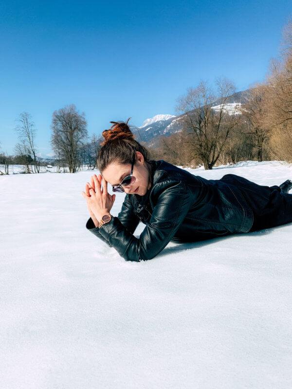 Frau liegt im Schnee und verschwendet ihre Zeit mit Niksen
